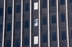 Defekte Jalousie im Fenster eines Bürogebäudes. Broken shutter in the window of an office building.