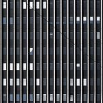 Fassade mit teilweise defekten Jalousien an einem Bürogebäude. Front of an office building with several broken shutters.
