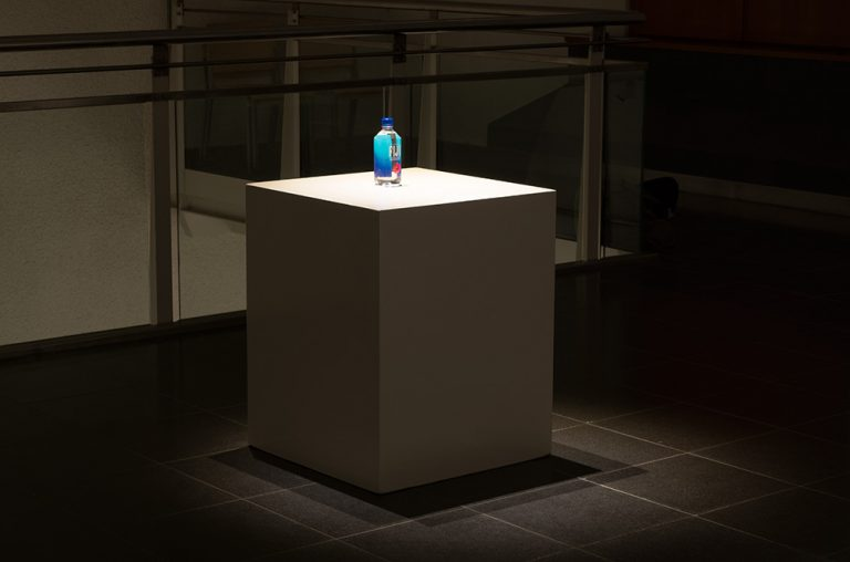 Bottle of Fiji Water (mineral water) on a plinth, exhibition view